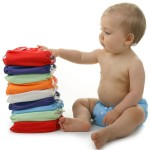 a baby and a stack of diapers